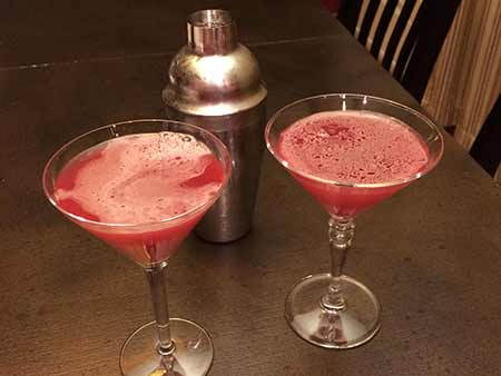 A shaker and two cosmopolitans in martini glasses